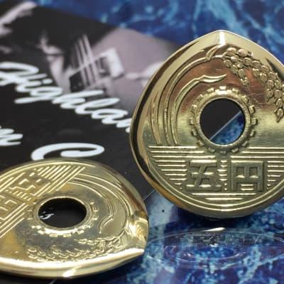 The Highland Plectrum Co. One Japanese 5 Yen Brass Coin Plectrum.